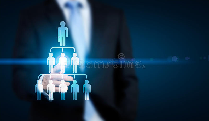 Businessman pointing at hierarchy. Delegate concept with businessman pointing at abstract employee hierarchy pictogram stock image