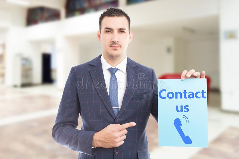Businessman pointing at contact us paper. Businessman pointing with index finger at contact us text and phone symbol blue paper royalty free stock photos