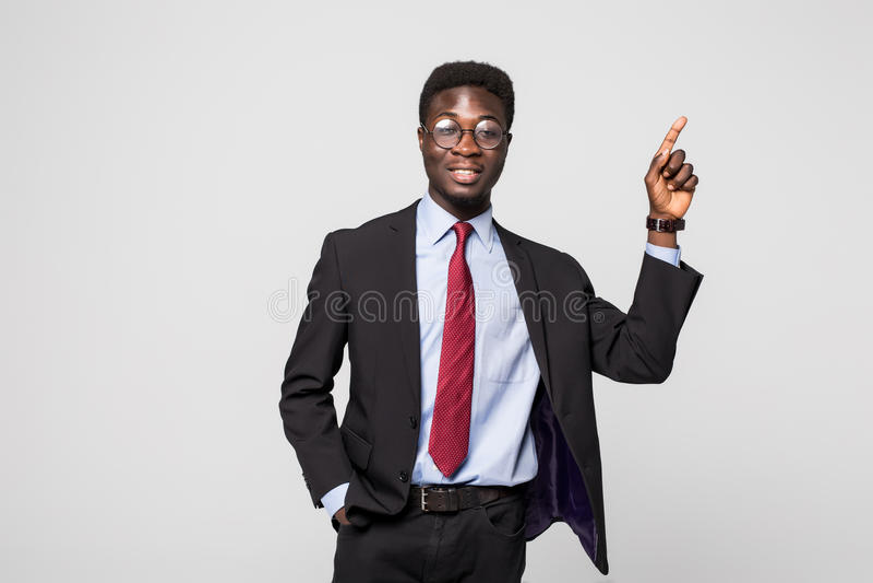 Businessman pointing at something on grey background stock image