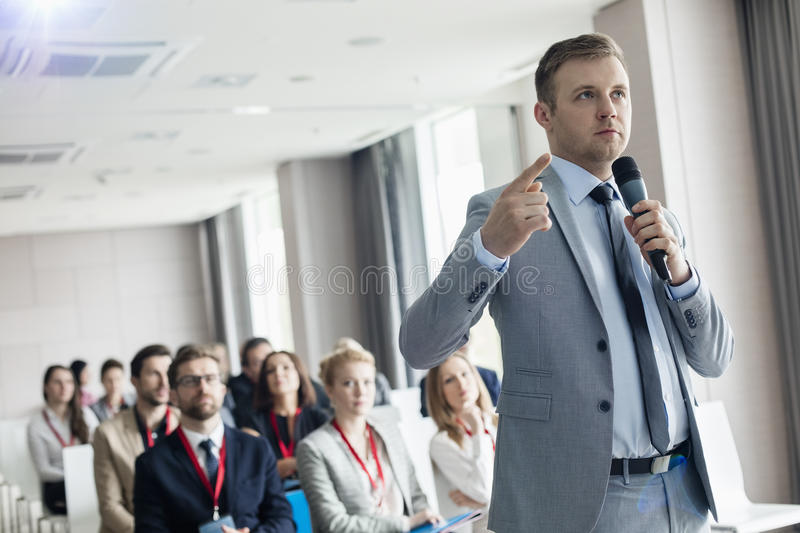 Businessman pointing while speaking through microphone during seminar in convention center.  stock photo