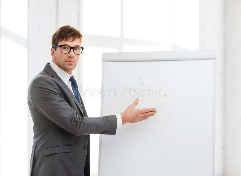 Download Businessman Pointing To Flip Board In Office Stock Photo - Image: 34984990