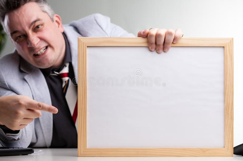 Businessman pointing to a handheld blank frame stock photos