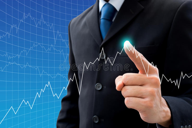 Businessman pointing to the peak. Businessman in dark gray suit pointing to the highest point of the graph stock photography