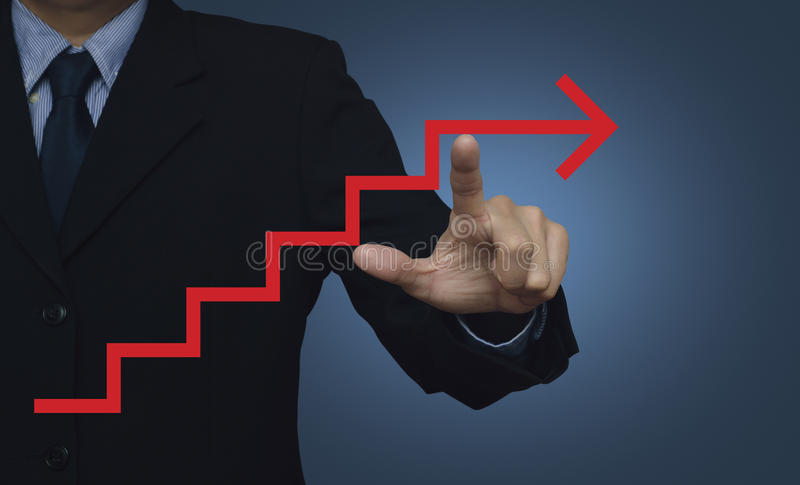 Businessman pointing to red arrow stair symbol on blue background, success concept stock photo