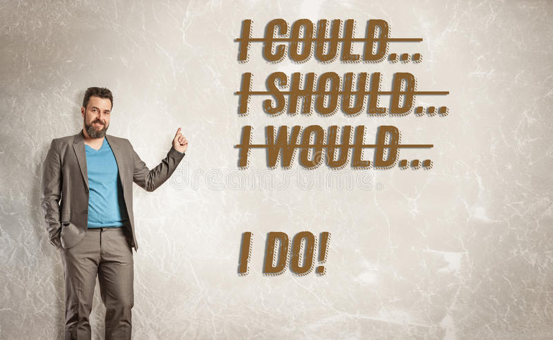 Businessman pointing to text, I could, should, would, I do. Grunge wall background stock image