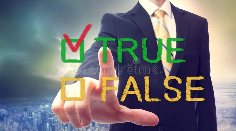 Businessman pointing TRUE. Businessman pointing at TRUE or FALSE checkbox stock image