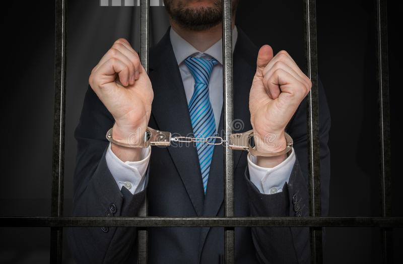 Businessman or politician with handcuffs behind bars in prison cell stock images