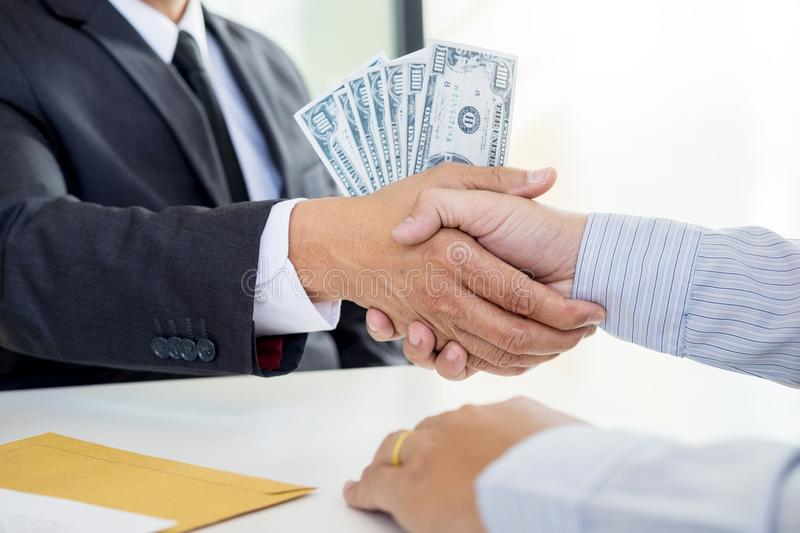 Businessman or politician taking bribe and Shaking Hands With Money in a suit, corruption trade exchange concept stock photography