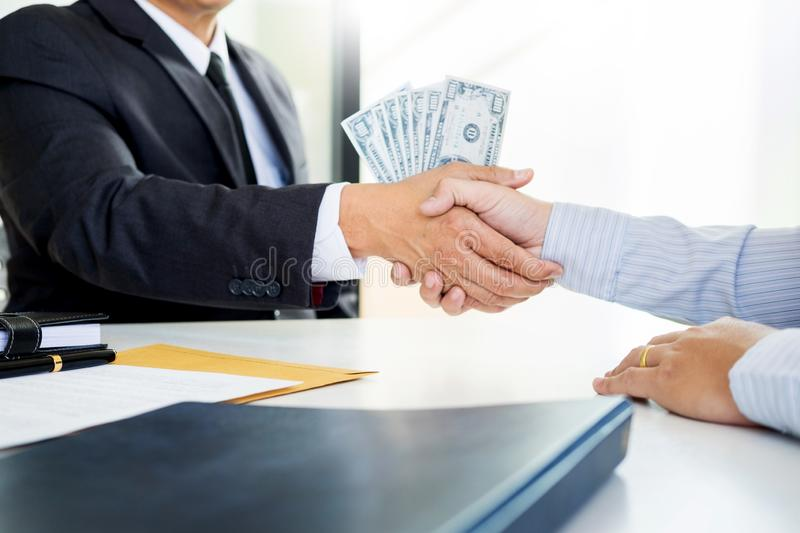 Businessman or politician taking bribe and Shaking Hands With Money in a suit, corruption trade exchange concept royalty free stock image