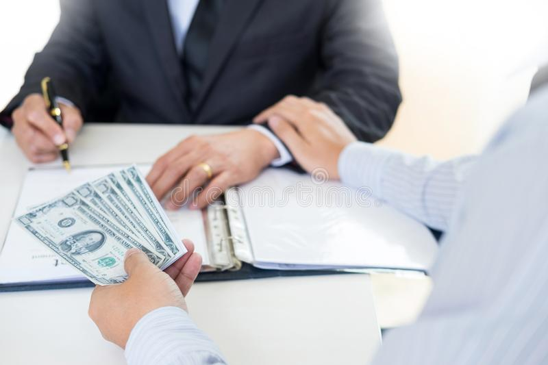 Businessman or politician taking bribe and Shaking Hands With Money in a suit, corruption trade exchange concept royalty free stock images