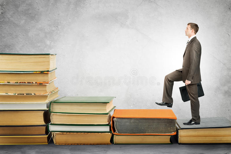 Businessman with portfolio goes up stairs of books stock photos