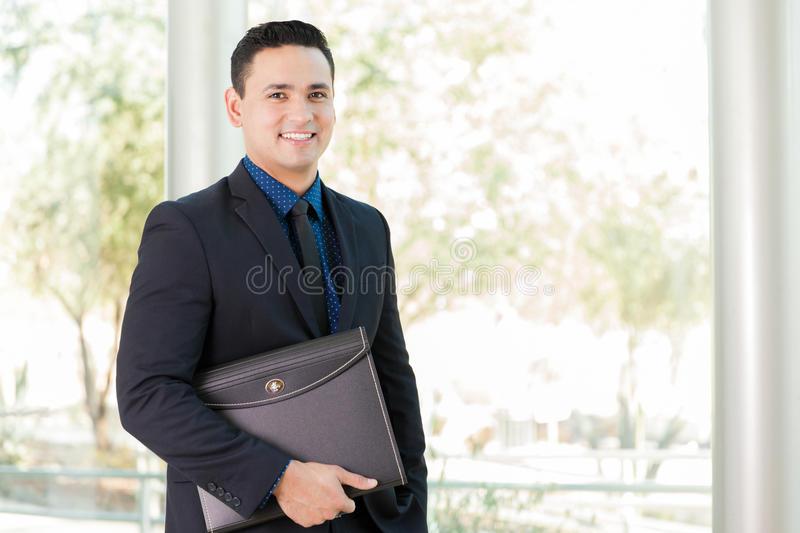 Businessman with a portfolio. Portrait of a young Latin businessman carrying a portfolio at work royalty free stock photos
