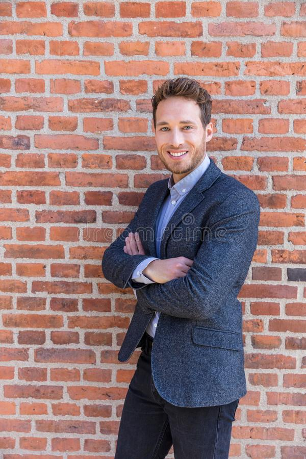 Businessman portrait on brick wall background. Young confident smiling man standing arms crossed royalty free stock image