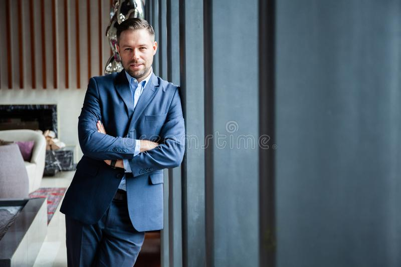 Businessman portrait. Happy confident young businessman standing arms crossed, smiling, looking at camera stock photography