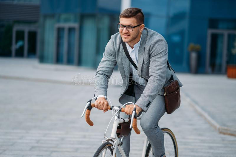 Businessman poses on bicycle at office building stock images