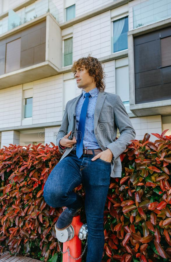 Businessman posing in the street. Young businessman with blazer and jeans leaning on a hydrant royalty free stock image
