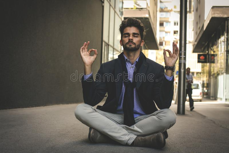 Businessman practicing yoga on the street. stock photos