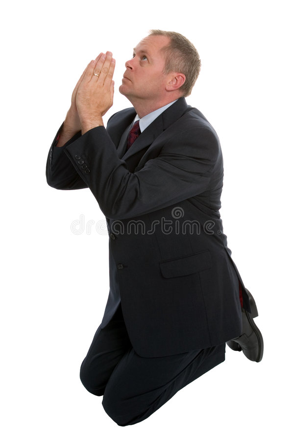 Businessman praying. Businessman on his knees praying stock image