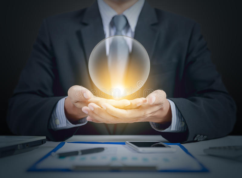 Businessman present crystal ball on hands. Business and finance concept stock images