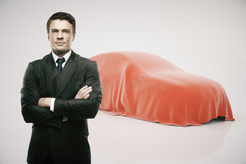 Businessman presenting new car. Businessman with crossed arms standing in front of car covered with red veil on light background. Car developer presenting new stock illustration