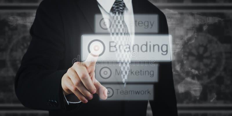 Businessman Pressing Button, Icons on Virtual Screen. Branding, Marketing, Strategy royalty free stock photo