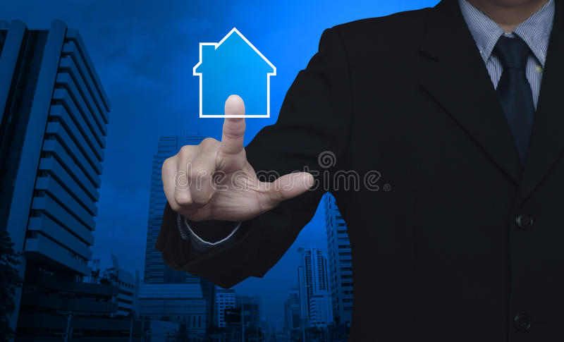 Businessman pressing house icon with copy space over city tower, Real estate concept stock photography