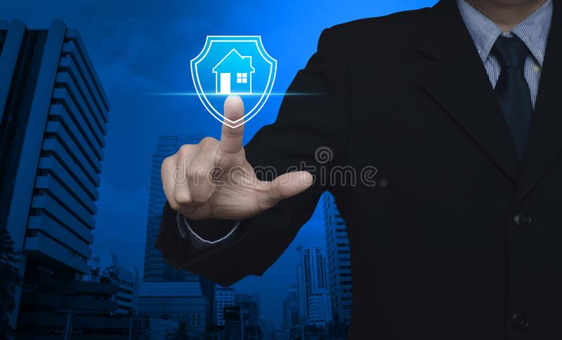 Business home insurance and security concept. Businessman pressing house with shield flat icon over modern office city tower and skyscraper, Business home stock photo