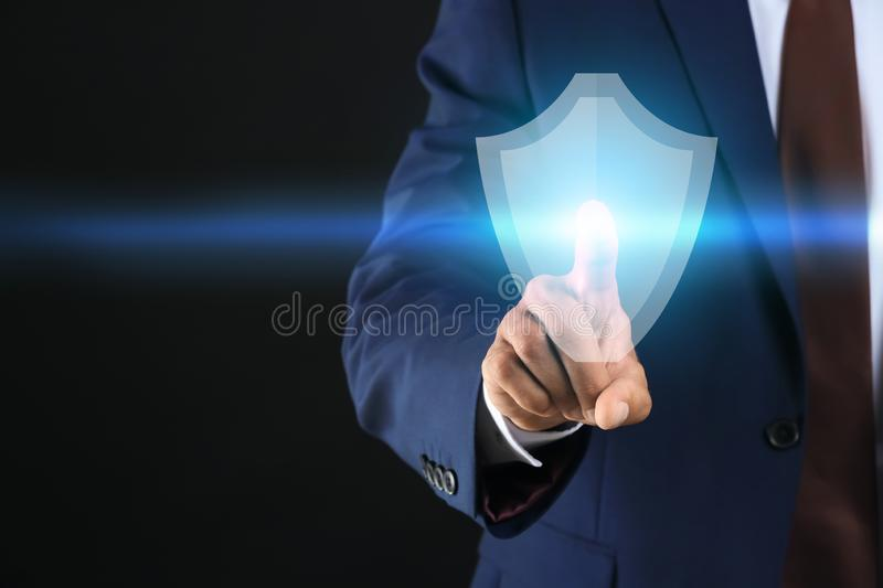 Businessman pressing shield icon on dark background. Data security concept stock image