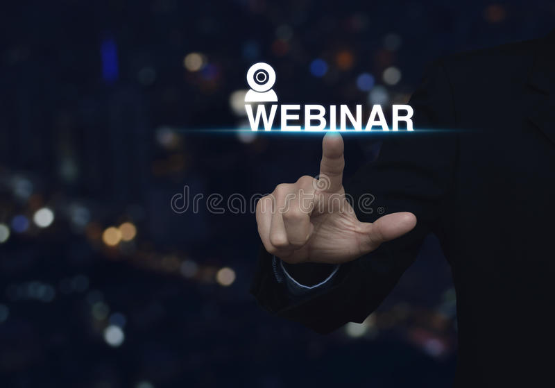 Businessman pressing webinar button over blurred night city tower background, Seminar online concept stock photography