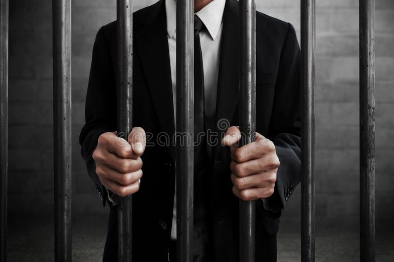 Businessman in prison hold bars stock image