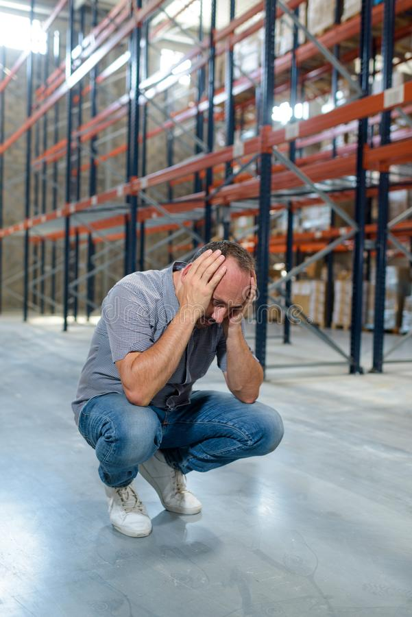 Businessman with problems in warehouse. Businessman with problems in a warehouse stock photo