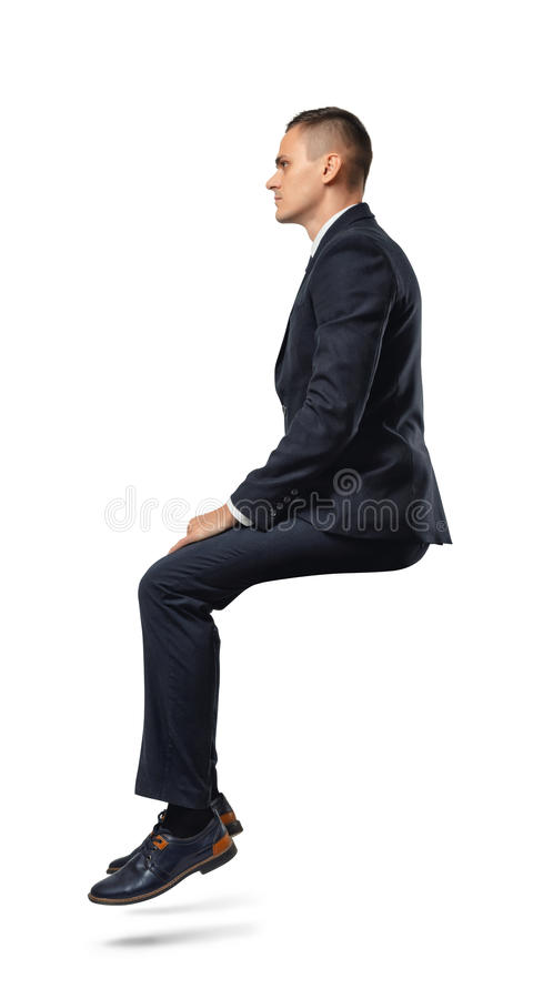 Businessman in profile in sitting position isolated on the white background. A businessman in profile in sitting position isolated on the white background royalty free stock image