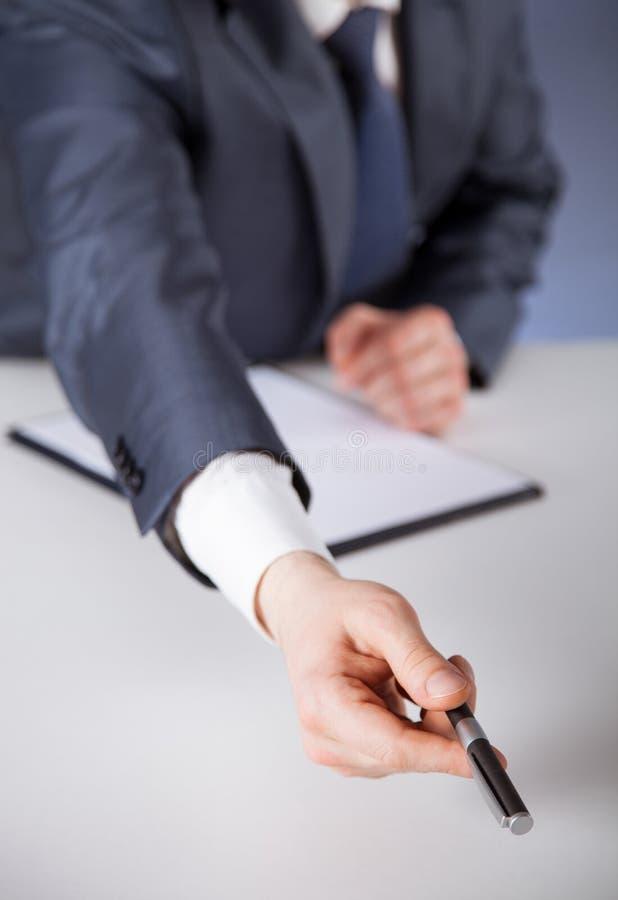 Businessman proposing to take a pen. Dark background royalty free stock photos