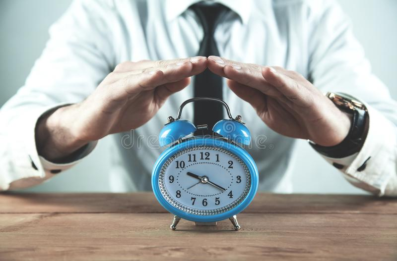 Businessman protect alarm clock. Business time management royalty free stock photo