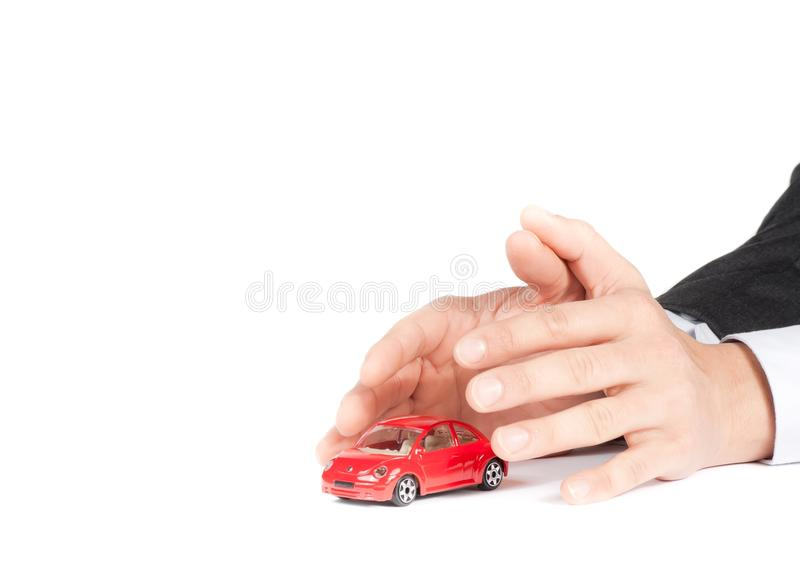 Businessman protect with his hands a red car, car insurance concept stock photo