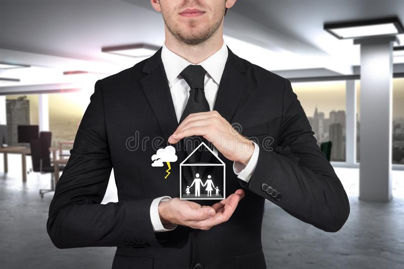 Businessman protecting family standing in house hands storm royalty free stock photo