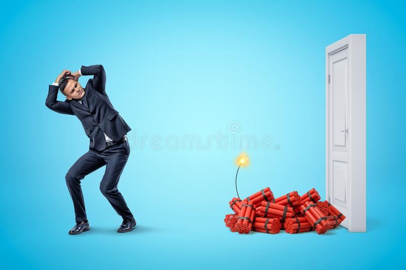 Businessman protecting himself with hands and red dynamite sticks with lit fuse next to white doorway on blue background stock photography