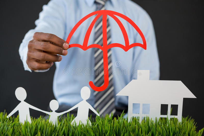 Businessman protecting paper cut out family, house and car with umbrella. Mid section of businessman protecting paper cut out family, house and car with umbrella stock photo