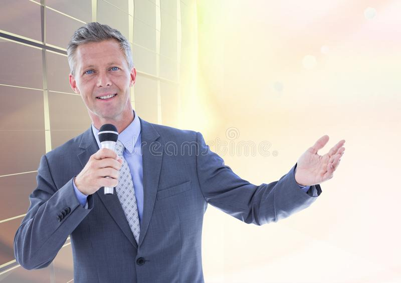 Businessman public speaking on microphone against bright sunlight stock photo