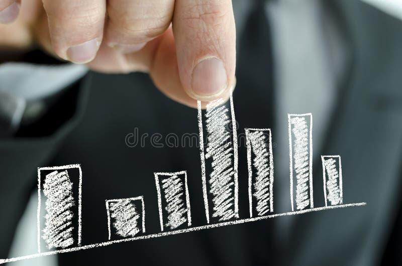 Businessman pulling graph column upwards stock photography