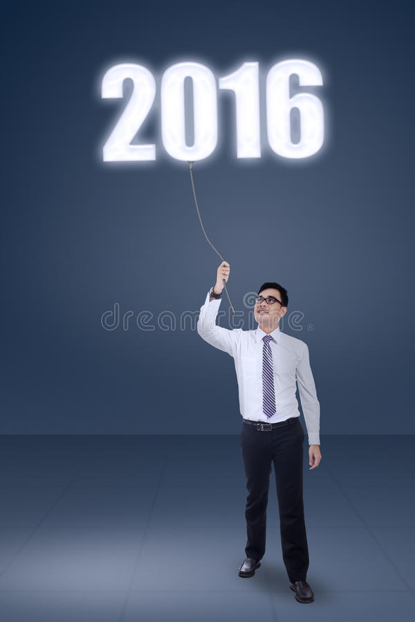 Businessman pulling number 2016 royalty free stock photo