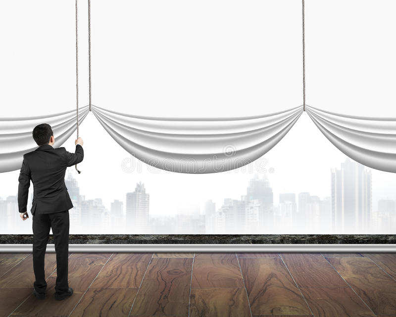 businessman pulling open blank white curtain covered gray cityscape background stock image