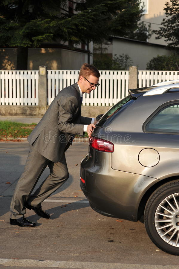 Businessman pushing a car royalty free stock image