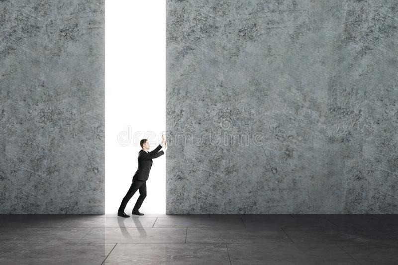 Opportunity and challenge concept. Businessman pushing concrete wall in interior. Opportunity and challenge concept stock image