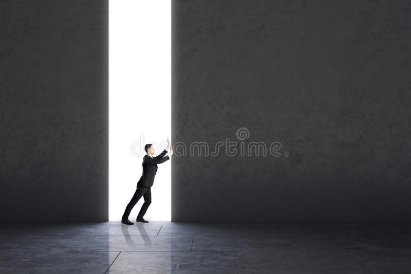 Opportunity and work concept. Businessman pushing concrete wall in interior. Opportunity and work concept royalty free stock image