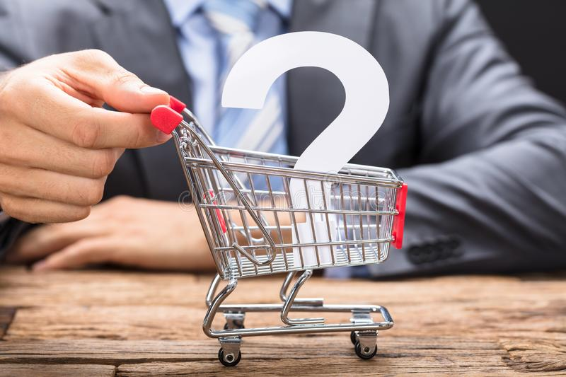Businessman Pushing Question Mark In Shopping Cart stock photography