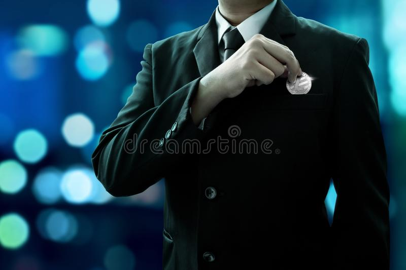Businessman put litecoin in the pocket. Businessman put litecoin on the pocket royalty free stock photos