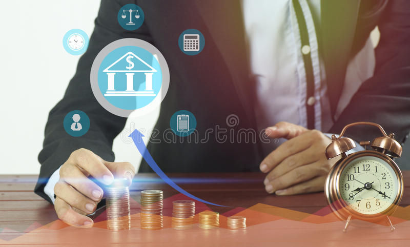 Businessman put money on pile of coins , concept in save money , fiance, account, loan and success. In business royalty free stock images