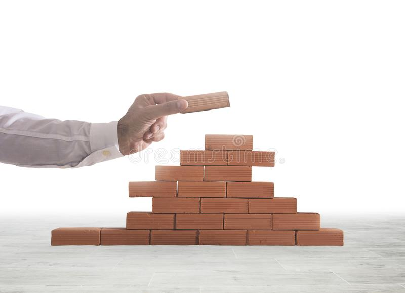 Businessman puts a brick to build a wall. Concept of new business, partnership, integration and startup stock photography