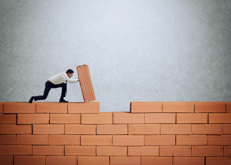Businessman puts a brick to build a wall. Concept of new business, partnership, integration and startup. Businessman puts a brick to build a big wall. Concept of royalty free stock photo